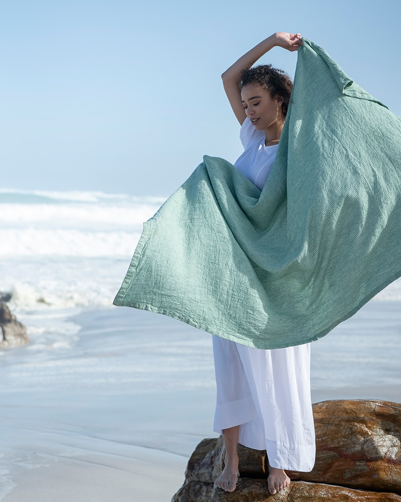 Modelling the Mungo Dhow Towel at Misty Cliffs beach. A 100% linen flat weave towel woven at the Mungo Mill in South Africa