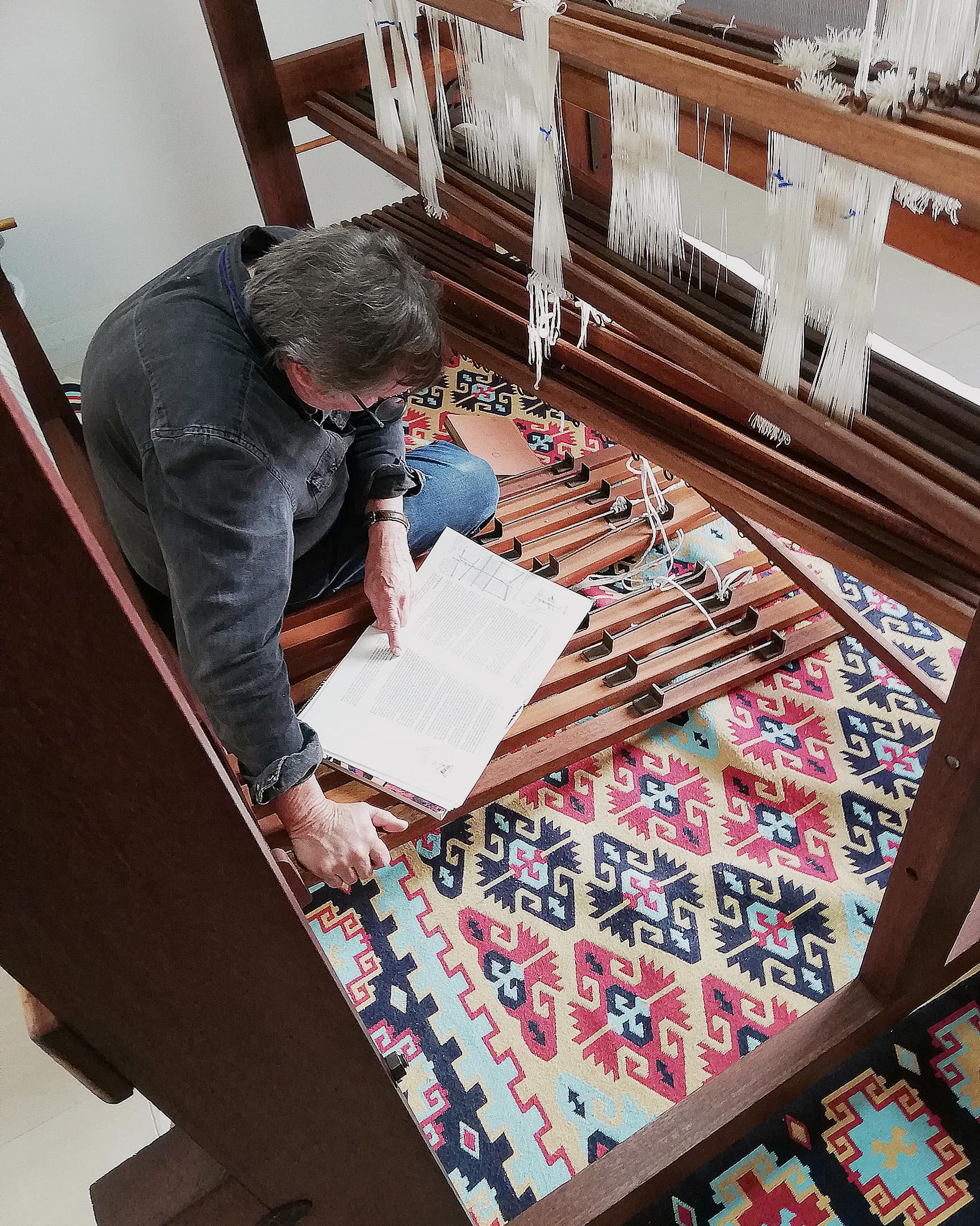 Mungo founder and Master Weaver, Stuart Holding reading a manual to help set up a hand weaving loom for Mungo head designer, Lenore