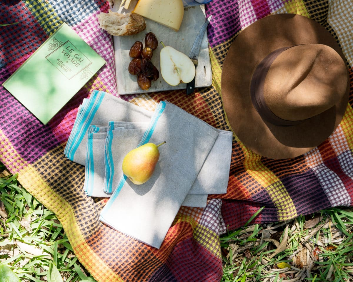Enjoying an outdoor picnic in the dappled sunlight - with a book, cheeseboard, fresh fruit and Vrou-Vrou blanket